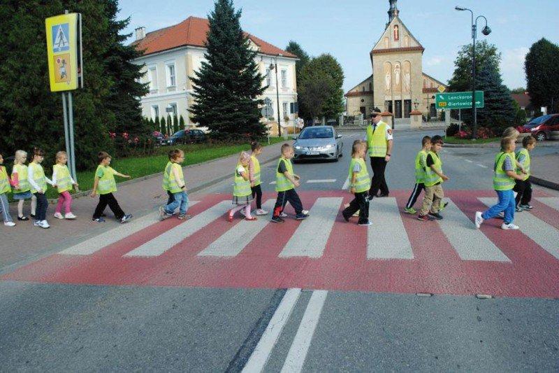 dzieci przechodzące przez jezdnię w kamizelkach odblaskowych