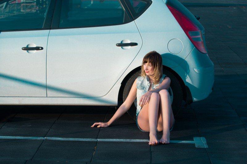 kobieta siedząca obok samochodu