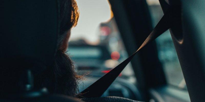 pasażer jadący samochodem zapięty pasami