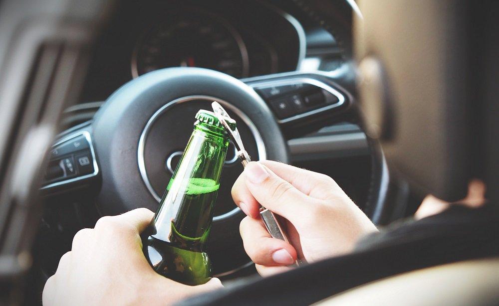 mężczyzna otwierający alkohol w samochodzie