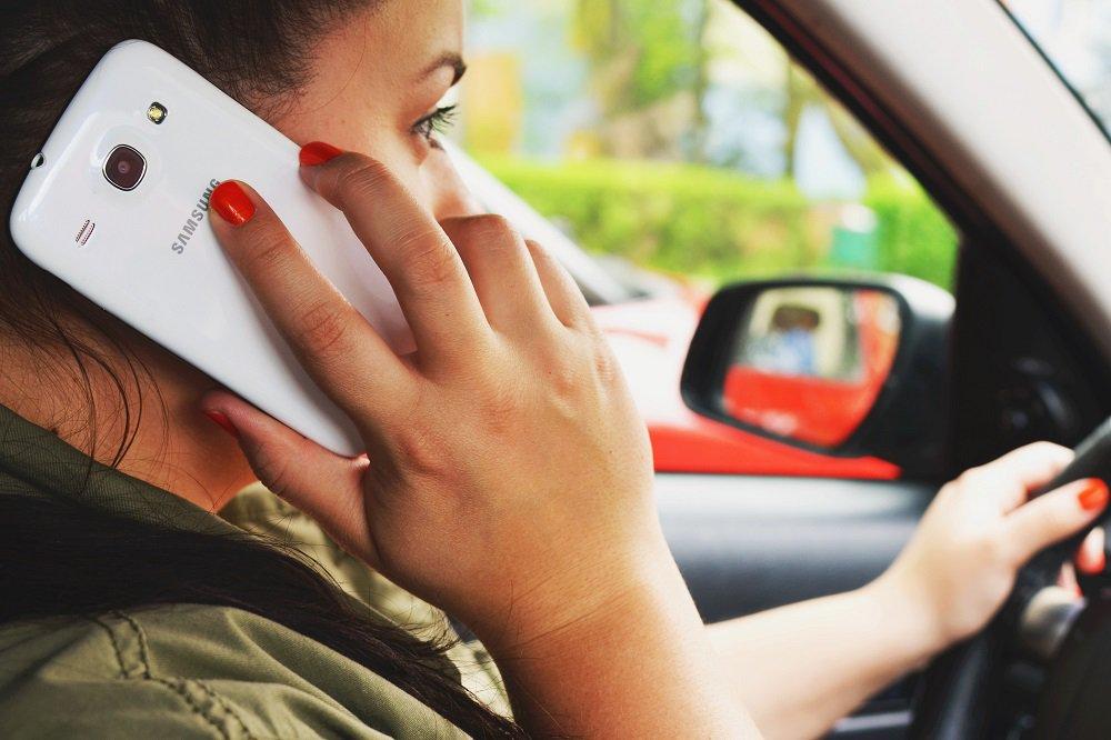 kobieta rozmawiająca przez telefon w trakcie jazdy samochodem