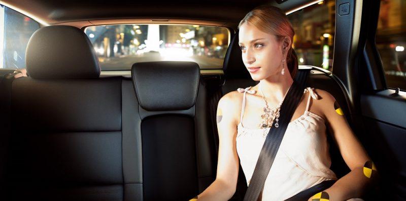 kobieta siedząca na tylnym siedzeniu samochodu zapięta pasami