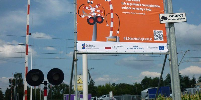 """banner reklamowy """" W razie awarii lub zagrożenia na przejeździe, zobacz co mamy z tyłu """""""