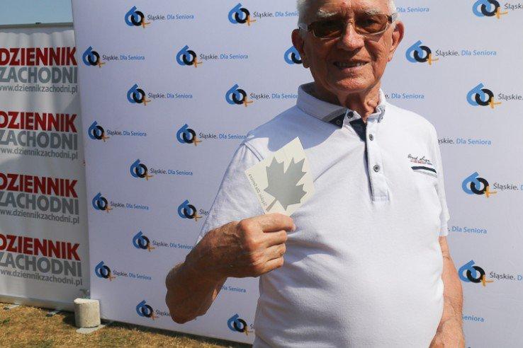 mężczyzna trzymający w ręku srebrny listek